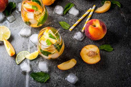 夏の飲み物を飲みます。ライム、ピーチ、ミント、桃のモヒート。暗い石のテーブルに食材を使用。 コピー スペース平面図 写真素材