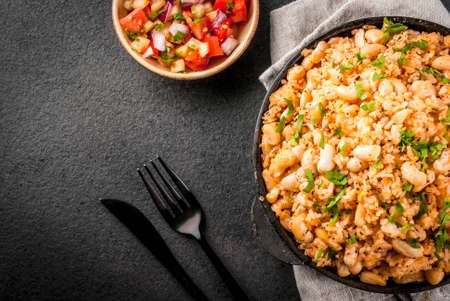 Mexican, Latin American cuisine. Mexican Rice and Beans Bowl is a recipe made with rice and white beans, homemade, with fresh herbs and herbs. In a frying pan for cooking, with salsa, top view copy space Reklamní fotografie