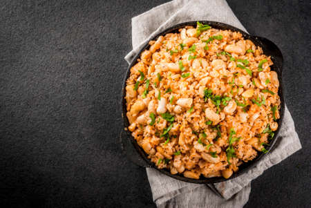 Mexican, Latin American cuisine. Mexican Rice and Beans Bowl is a recipe made with rice and white beans, homemade, with fresh herbs and herbs. In a frying pan for cooking, top view copy space Reklamní fotografie