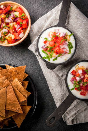 Mexican, LatinAmerican cuisine. Queso blanco recipe - cream cheese, cream, fresh stewed vegetables tomatoes, onions, peppers,  herbs. With Baked Tortilla Chips, black stone table. Top view copy space