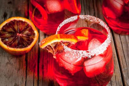 さわやかな夏の飲み物。オレンジの飾りと木製の素朴なテーブル上のグラス、カクテルのブラッディ オレンジ マルガリータ