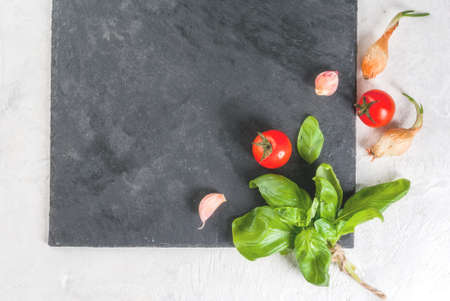 Food background. Ingredients, greens and spices for cooking lunch, lunch. Fresh basil leaves, tomatoes, garlic, onions, salt, pepper. On a white stone table, a slate board. Top view copy space