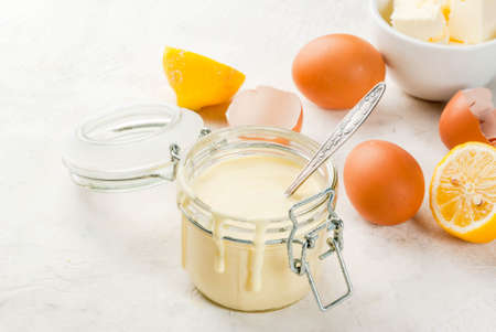 Traditional basic sauces. French cuisine. Hollandaise sauce in glass jar, with ingredients for cooking - eggs, butter, lemons. On a white concrete stone table. Copy space Stock Photo