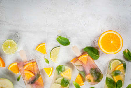 Homemade ice cream. Frozen drinks. Fresh fruits, citrus. Popsicles of red, white sangria, lemonade or mojito. With oranges, lime, mint, apples. White stone table, ingredients. top view copy space