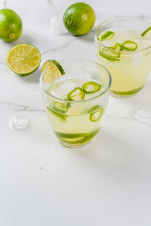 Mexican traditional refreshing drink Fresh Lime and Jalapeno Margarita with tequila, hot pepper and lime (lemon). On a white marble kitchen table. Copy space