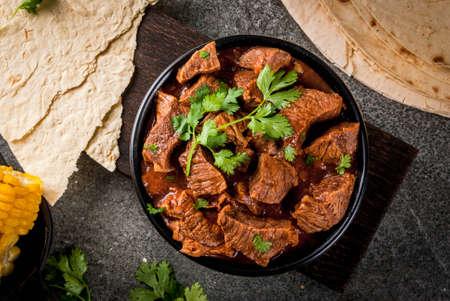 Mexicaans en Amerikaans traditioneel eten. Hutspotrundvlees met tomaten, kruiden, peper - Chili Colorado. Met tortilla's. Ruimte kopiëren, op zwarte stenen tafel