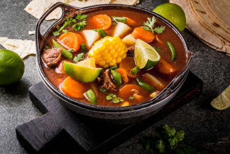 Autumnal vegetable stew. Mexican traditional vegetable soup Mole de olla with meat, potatoes, carrots, beans, corn and lime. Copy space Imagens