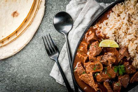 Cuisine traditionnelle mexicaine et américaine. Stew beef with tomatoes, spices, pepper - Chile Colorado. Avec du riz bouilli. La citron vert, les tortillas. Vue en haut de l'espace de copie. Sur la table de pierre noire Banque d'images - 82502303