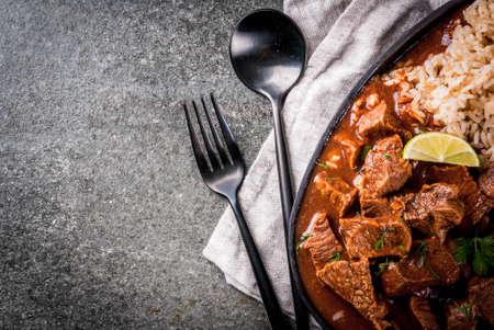 Mexicaans en Amerikaans traditioneel eten. Stoofvleesrundvlees met tomaten, kruiden, peper - Chili Colorado. Met gekookte rijst. limoen, tortilla's. Ruimte bovenaanzicht kopiëren. Op zwarte stenen tafel Stockfoto - 82502302