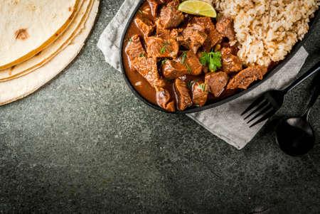 Mexicaans en Amerikaans traditioneel eten. Stoofvleesrundvlees met tomaten, kruiden, peper - Chili Colorado. Met gekookte rijst. limoen, tortilla's. Ruimte bovenaanzicht kopiëren. Op zwarte stenen tafel Stockfoto