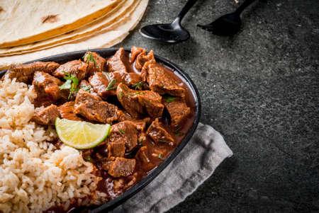 Mexicaans en Amerikaans traditioneel eten. Stoofvleesrundvlees met tomaten, kruiden, peper - Chili Colorado. Met gekookte rijst. limoen, tortilla's. Ruimte kopiëren. Op zwarte stenen tafel