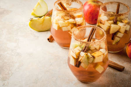 Autumn and winter drinks. Warm apple sangria, apple cider with pieces of fruit, cinnamon, spices, sugar. In glasses, on a stone beige table. With the ingredients. Copy space