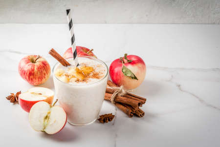 Healthy vegan food. Dietary breakfast or snack. Apple pie smoothies, with apples, yogurt, cinnamon, spices, walnuts. In a glass, on a white marble table. Copy space