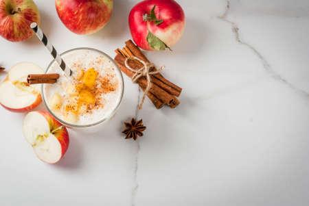 健康な菜食主義者料理。食事朝食やおやつ。リンゴ、ヨーグルト、シナモン、スパイス、クルミとアップルパイ スムージー。白い大理石のテーブル 写真素材