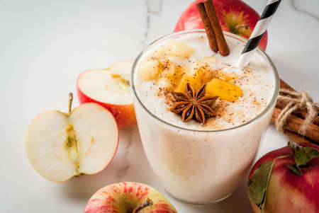 Healthy vegan food. Dietary breakfast or snack. Apple pie smoothies, with apples, yogurt, cinnamon, spices, walnuts. In a glass, on a white marble table. Copy space Stock Photo