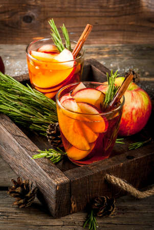 Christmas, Thanksgiving drinks. Autumn, winter cocktail grog, hot sangria, mulled wine - apple, rosemary, cinnamon, anise. On old rustic wooden table, tray. With cones, rosemary branches. Copy space Banque d'images