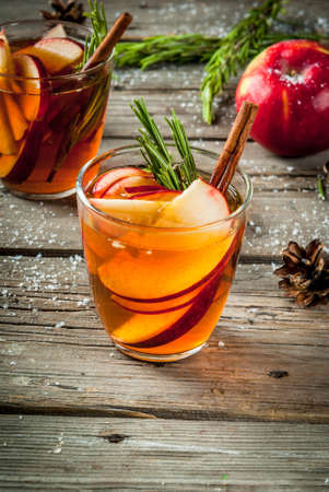 Christmas, Thanksgiving drinks. Autumn, winter cocktail grog, hot sangria, mulled wine - apple, rosemary, cinnamon, anise. On old rustic wooden table. With cones, rosemary branches. Copy space
