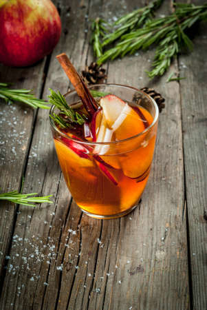 spice: Christmas, Thanksgiving drinks. Autumn, winter cocktail grog, hot sangria, mulled wine - apple, rosemary, cinnamon, anise. On old rustic wooden table. With cones, rosemary branches. Copy space