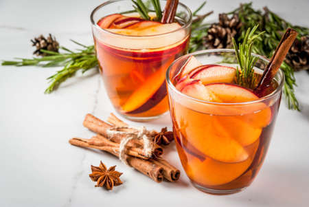 Christmas, Thanksgiving drinks. Autumn, winter cocktail grog, hot sangria, mulled wine - apple, rosemary, cinnamon, anise. On white marble table. With cones, rosemary. Copy space