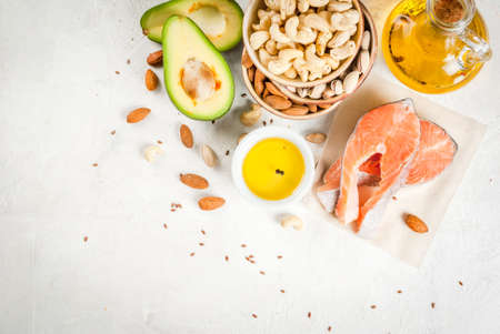 Gezond eten. Producten met gezonde vetten. Omega 3, omega 6. Ingrediënten en producten: forel (zalm), lijnzaadolie, avocado, amandelen, cashewnoten, pistachenoten. Op een witte stenen tafel. Ruimte bovenaanzicht kopiëren Stockfoto