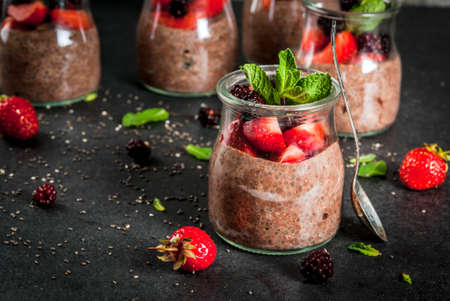 Healthy vegan breakfast. Dessert. Alternative food. Pudding with chia seeds, fresh strawberries, blackberries and mint. On a dark stone background. Copy space Zdjęcie Seryjne