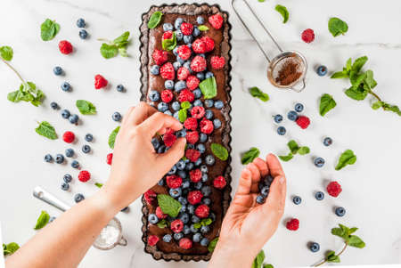 Summer homemade baked pastry. Chocolate cake tart with chocolate cream, woman decorate it with blueberry raspberry mint leaves, powdered sugar. White marble table, copy space top view hands in picture Stok Fotoğraf - 82932428