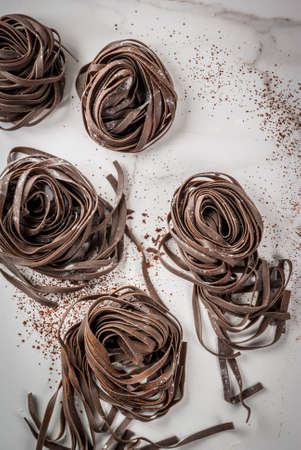 Raw unprepared chocolate pasta noodles. On a white kitchen marble table. Copy space top view 版權商用圖片