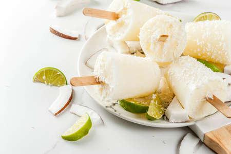 여름 디저트. 채식주의 자의 다이어트 식품. 스틱에 코코넛과 라임 홈 과일 아이스크림 캔디. 흰색 대리석 테이블에 복사본 공간