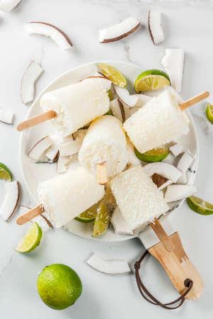 여름 디저트. 채식주의 자의 다이어트 식품. 스틱에 코코넛과 라임 홈 과일 아이스크림 캔디. 흰색 대리석 테이블, 복사 공간 상위 뷰