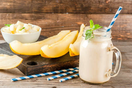 Smoothie of yogurt, raw organic yellow melon, flax seeds and mint. With striped straws, in mason jar, wooden rustic table, copy space Stok Fotoğraf