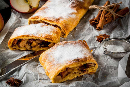 Home autumn, summer baking, puff pastries. Apple strudel with nuts, raisins, cinnamon and powdered sugar. On a wooden old rustic table. Sliced, with ingredients. Copy space