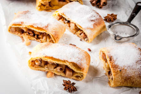 Home autumn, summer baking, puff pastries. Apple strudel with nuts, raisins, cinnamon and powdered sugar. On white marble table. Sliced, with ingredients. Copy space