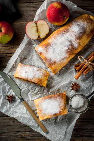 Home autumn, summer baking, puff pastries. Apple strudel with nuts, raisins, cinnamon and powdered sugar. On a wooden old rustic table. Sliced, with ingredients. Copy space top view Stock Photo