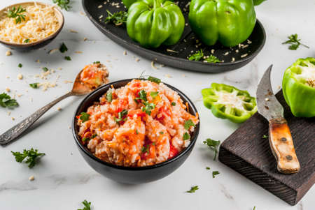 Autumn recipes. Home stuffed bell pepper with minced meat, carrots, tomatoes, herbs and cheese. Cooking process. On a white marble table.  Copy space