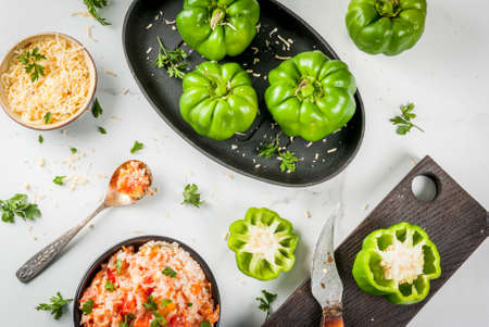Autumn recipes. Home stuffed bell pepper with minced meat, carrots, tomatoes, herbs and cheese. Cooking process. On a white marble table. Top view. Copy space Stock Photo