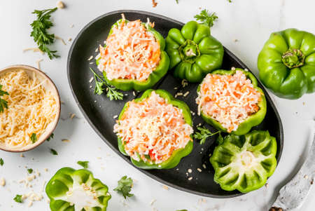Autumn recipes. Home stuffed bell pepper with minced meat, carrots, tomatoes, herbs, cheese. Cooking process. White marble table. Stuffed pepper ready for baking, in pan, Copy space top view