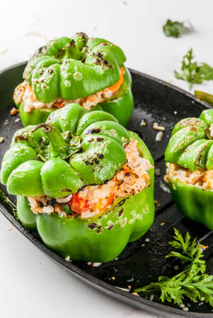 Autumn recipes. Homemade stuffed bell pepper with minced meat, carrots, tomatoes, herbs, cheese. On white marble table, in baking pan, Copy space