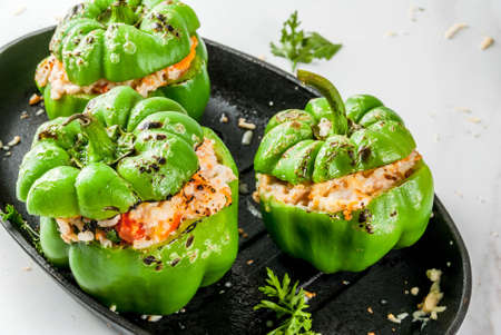 Autumn recipes. Homemade stuffed bell pepper with minced meat, carrots, tomatoes, herbs, cheese. On white marble table, in baking pan, Copy space 版權商用圖片 - 83157423