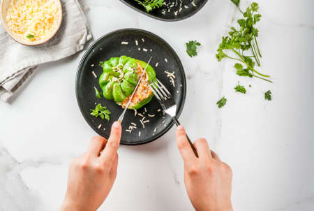 Autumn recipes. Woman eats homemade stuffed bell pepper with minced meat, carrots, tomatoes, herbs, cheese. On white marble table, in portioned plate, hands in picture, Copy space top view