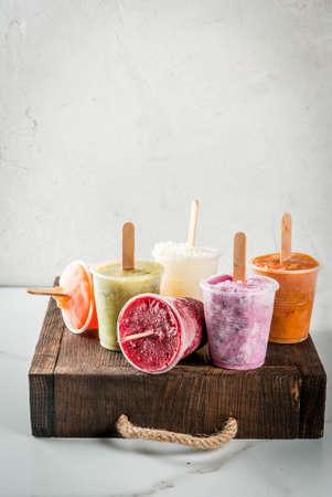 健康的な夏のデザート。アイスクリーム ・ アイスキャンディー。冷凍トロピカル ジュース、スムージー ブルーベリー。スグリ、オレンジ、マンゴ