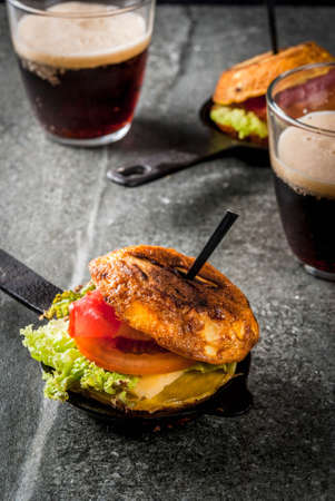 Mexican Tortilla de patatas rellena de jamón serrano - casserole with potato, eggs, sandwich with meat, lettuce, cheese, tomatoes. In portioned frying pans, with beer, black stone table.  Copy space