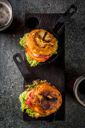 Mexican Tortilla de patatas rellena de jamón serrano - casserole with potato, eggs, sandwich with meat, lettuce, cheese, tomatoes. In portioned frying pans, with beer, black table.  Copy space above
