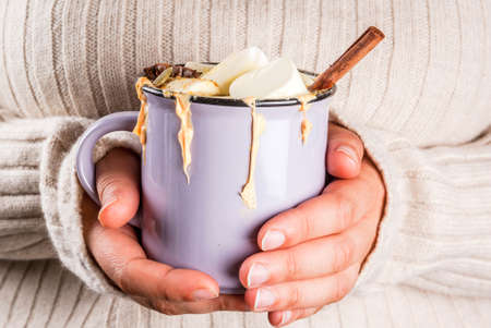 Autumn, winter drinks. Ideas for Christmas, Thanksgiving, Halloween. Girl drink hot spicy pumpkin white chocolate, with marshmallow, cinnamon, anise. With knitted plaid. Copy space, hands in picture
