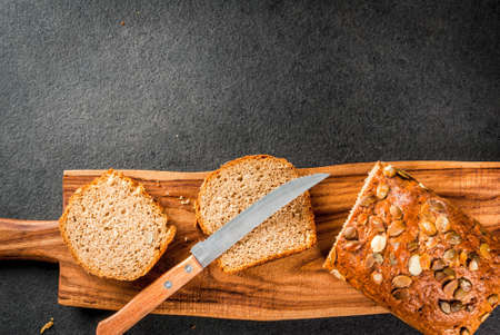 Freshly baked homemade organic multi-grain bread with pumpkin seeds on a cutting board on a black stone table. Copy space top view Stock Photo