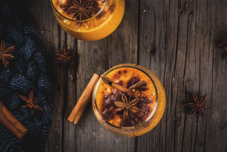 licuadora: Traditional autumn dishes, spicy pumpkin pie smoothie with cinnamon, anise and oatmeal. In portioned glasses, on rustic wooden old table. Copy space top view Foto de archivo