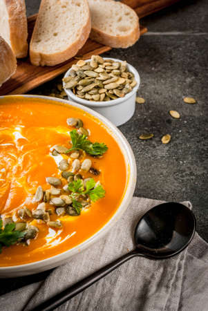 Traditional fall and winter dishes, hot and spicy pumpkin  soup with pumpkin seeds, cream and freshly baked baguette, on black stone table, copy space