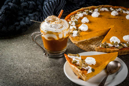 Traditional autumn dishes. Halloween, Thanksgiving. Spicy pumpkin pie with whipped cream & pumpkin seeds, pumpkin latte with cinnamon on black stone table with blanket. Copy space 스톡 콘텐츠