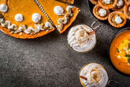 Set of traditional autumn food. Halloween, Thanksgiving. Spicy pumpkin latte, pumpkin pie and tartalets with whipped cream and pumpkin seeds, pumpkin soup, on black stone table. Copy space top view