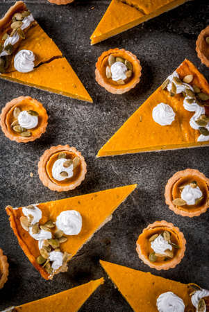 Traditional autumn dishes. Halloween, Thanksgiving. Set of spicy pumpkin pie and pumpkin tartlets with whipped cream & pumpkin seeds on black stone table. top view Stock Photo