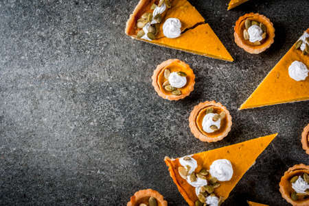 Traditional autumn dishes. Halloween, Thanksgiving. Set of spicy pumpkin pie and pumpkin tartlets with whipped cream & pumpkin seeds on black stone table. Copy space top view Stock Photo